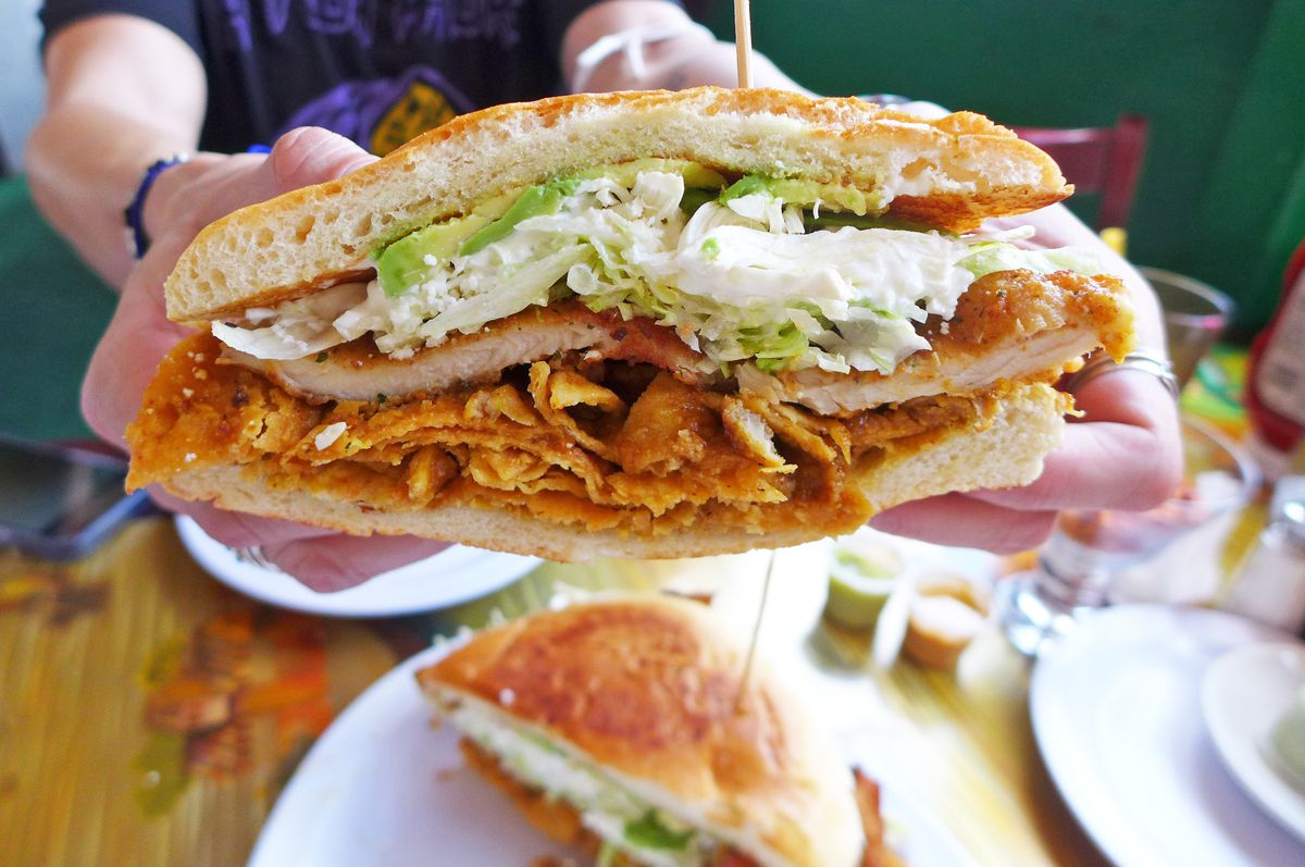 A sandwich held up by a pair of hands in which a fried cutlet and tortilla chips are visible.
