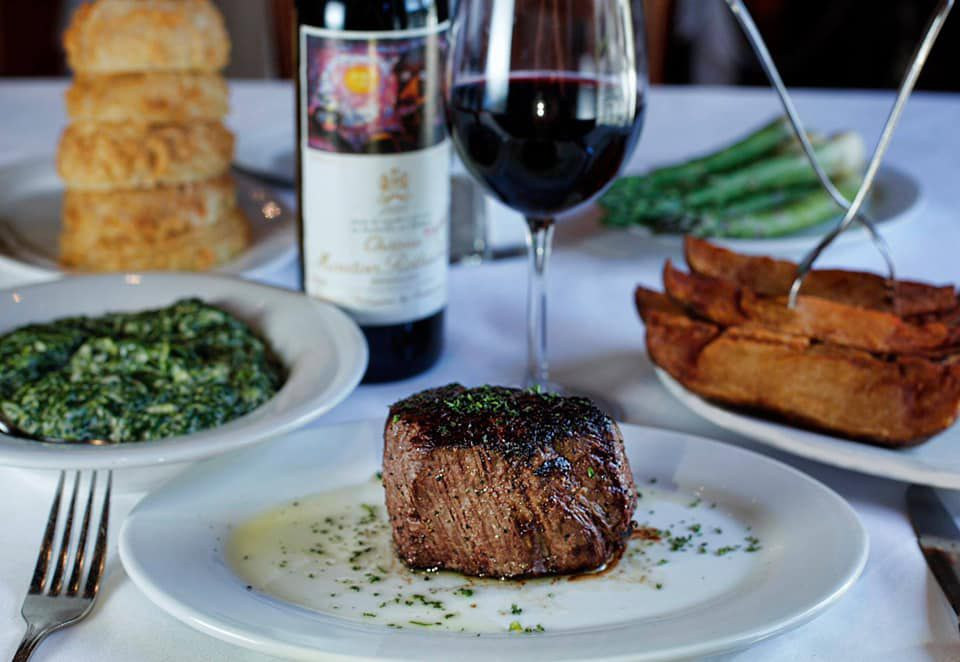 A table with plates of filet mignon, steak fries, creamed spinach, biscuits, asparagus stalks, a glass of red wine, and a wine bottle