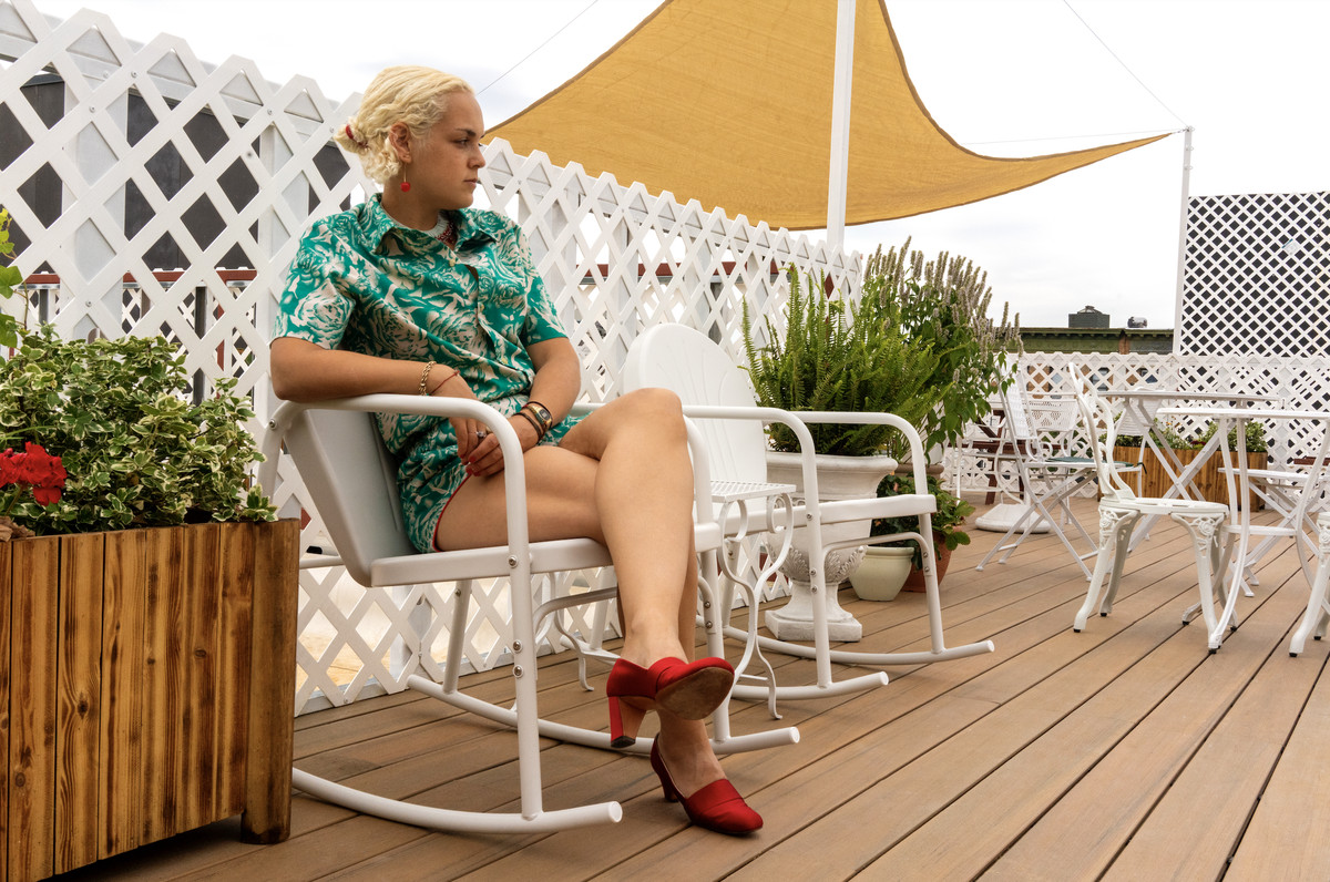 A person wearing a green shirt and red shoes sits in a white lawn chair on a rooftop deck.