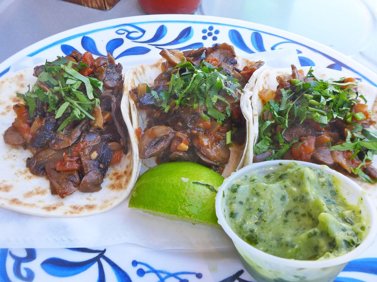 Three tortillas folded up with mushrooms inside on a Delft-blue plate.