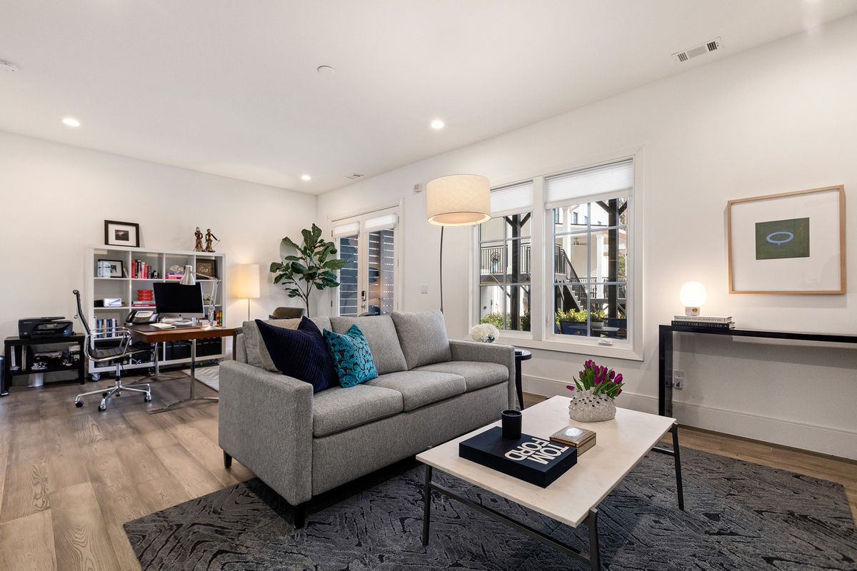 A white office with a townhome community visible out the windows.