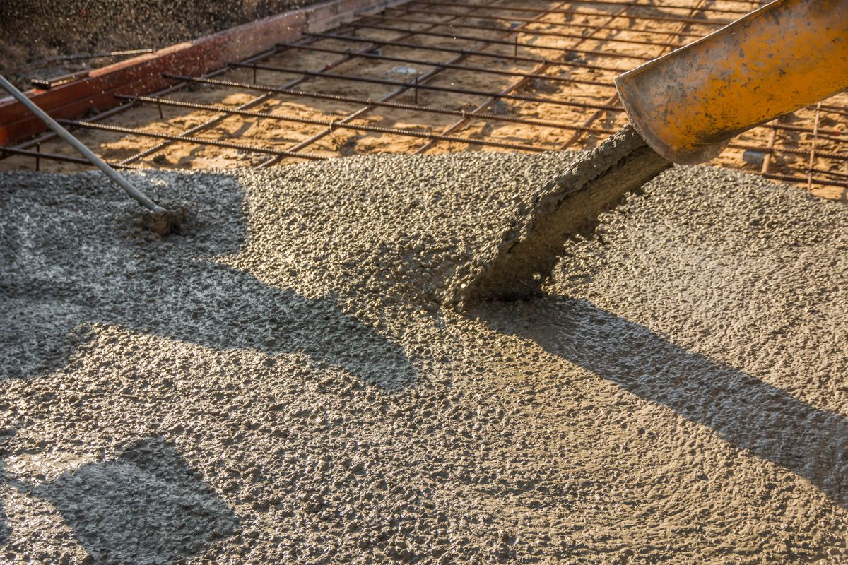 Concrete being poured onto a rebar grid.