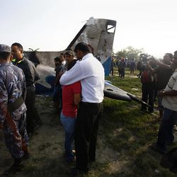 A Nepalese relative of a crew member is comforted at the crash site of a Sita Air airplane near Katmandu, Nepal, early Friday, Sept. 28, 2012.  The plane carrying trekkers into the Everest region crashed just after takeoff Friday morning in Nepal's capital, killing all 19 people on board, authorities said.