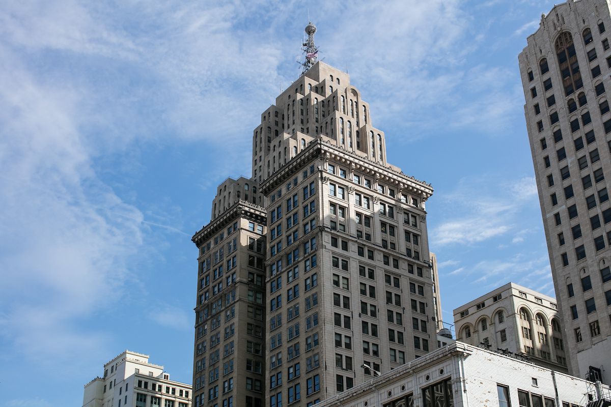 The exterior of the Penobscot Building in Detroit. The facade is white with a red beacon on top.