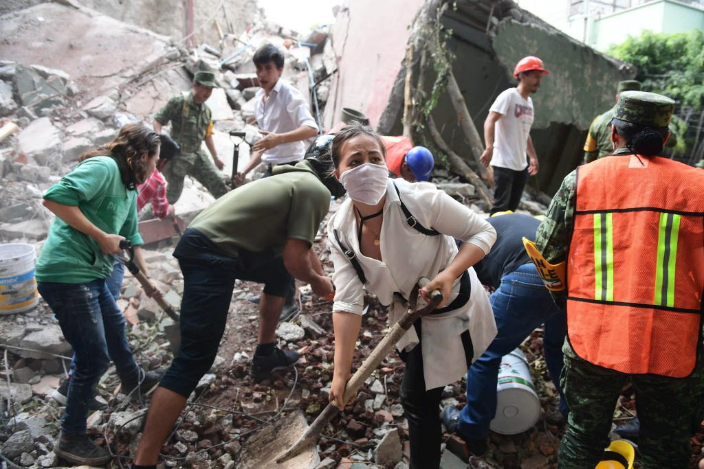 Rescuers, firefighters, policemen, soldiers and volunteers remove rubble and debris from a flattened building in search of survivors after a powerful quake in Mexico City on September 19, 2017. | Ronaldo Schemidt/AFP/Getty Images