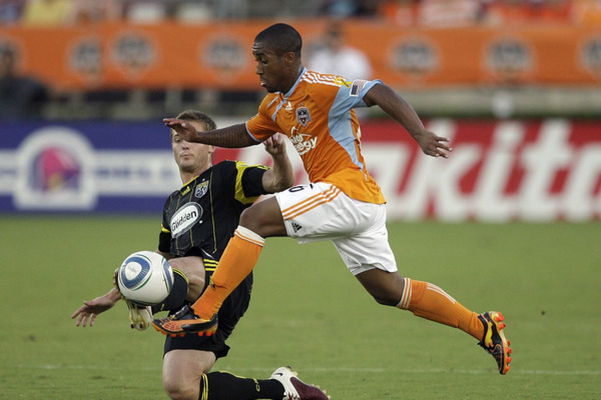 HOUSTON - JULY 10:  Corey Ashe #26 of the Houston Dynamo is tripped up by Robbie Rogers #18 of the Columbus Crew in the first half at Robertson Stadium  on July 10 2010 in Houston Texas.  (Photo by Bob Levey/Getty Images)