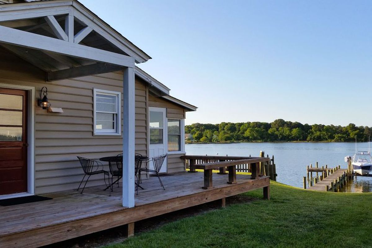 A waterfront cottage in Cobb Island, Maryland, with beige siding, a wood deck, and a dock.