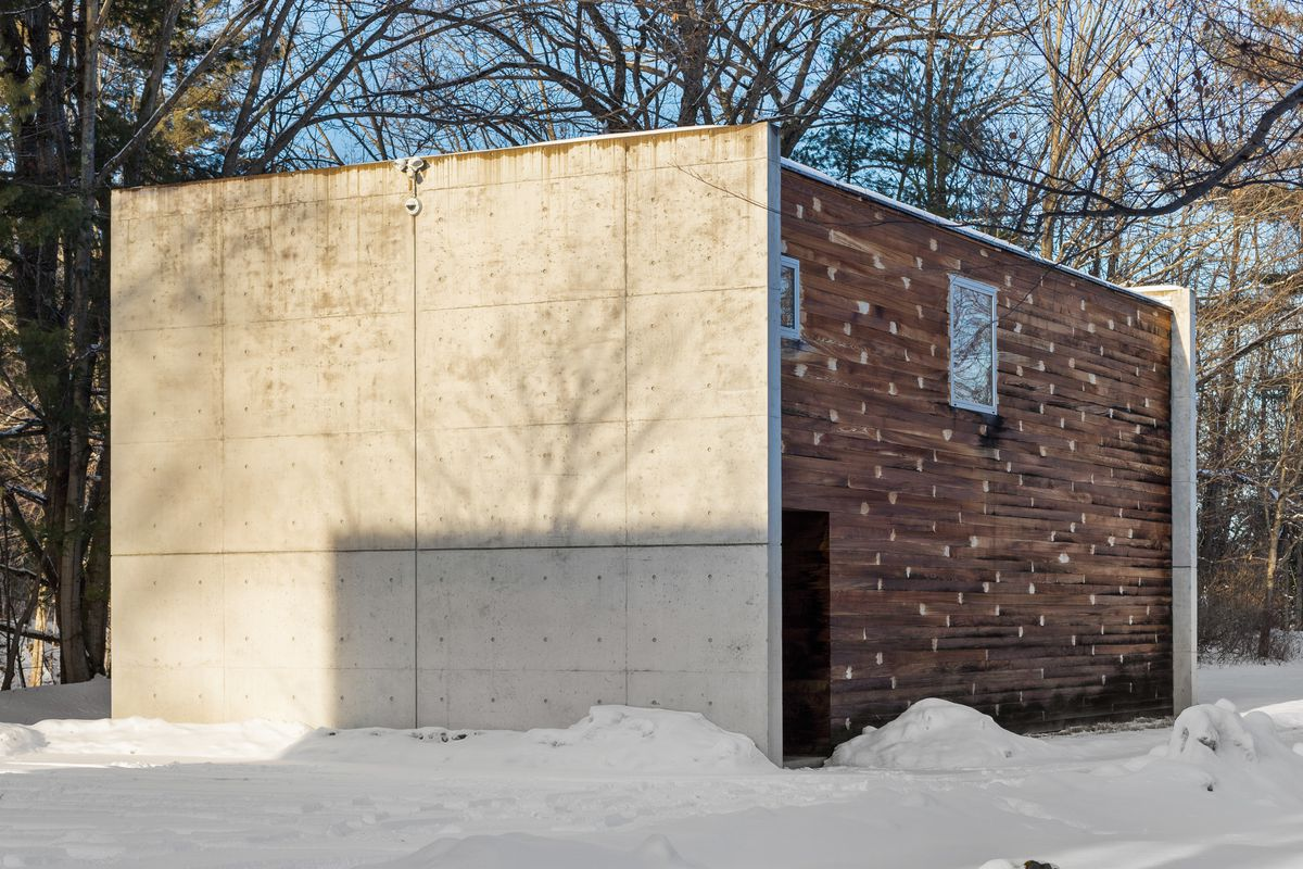 A concrete building sits in a snowy field. On one side there is wood siding.