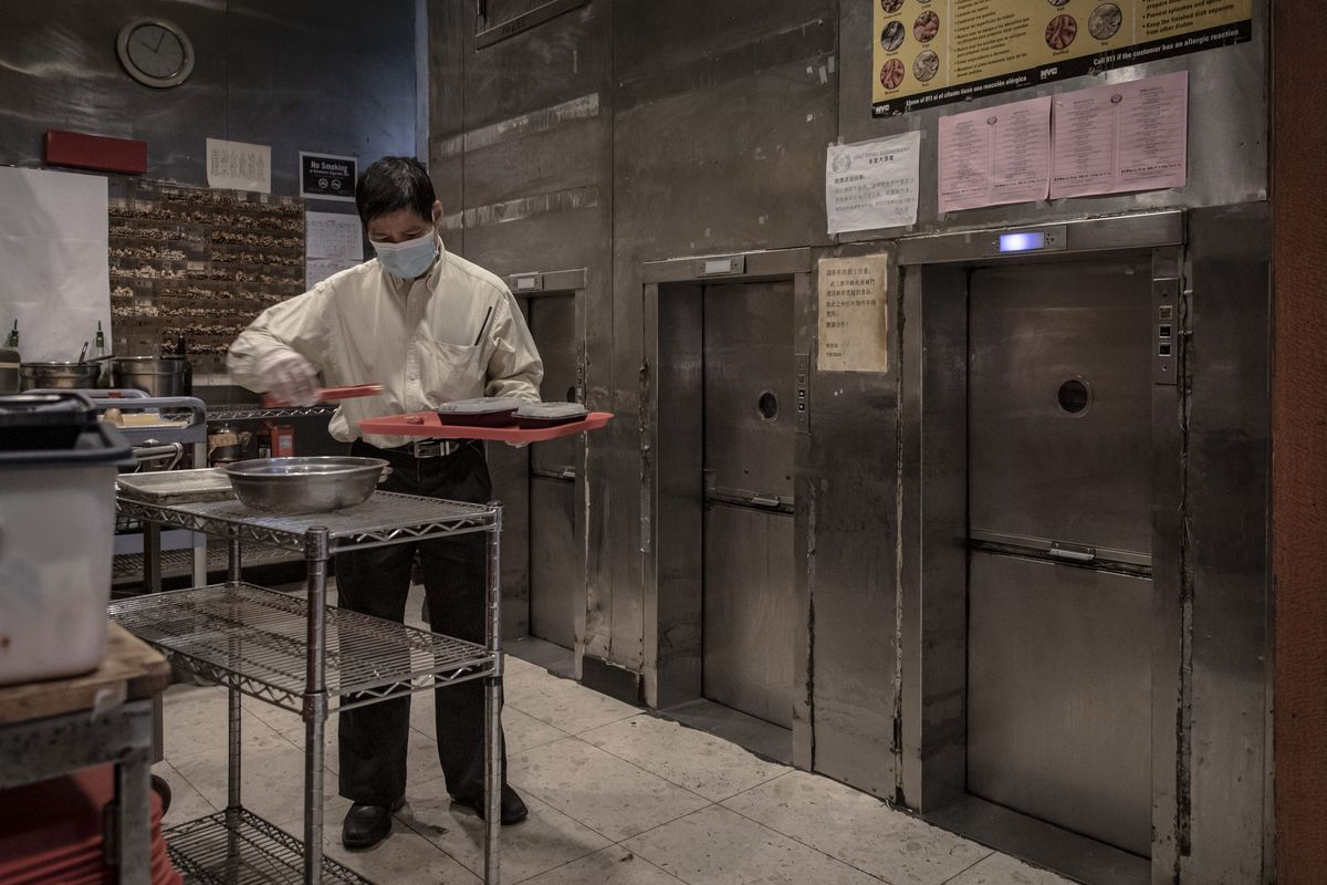 A waiter places food on trays in front of a dumbwaiter