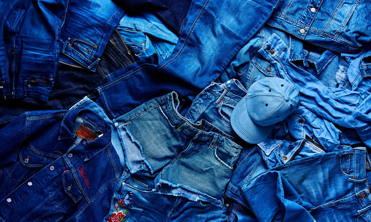 Jeans and other denim items, laid out on the floor.