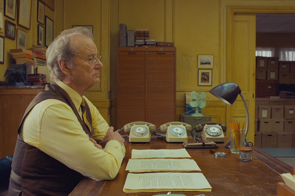 Bill Murray, in tweed and shirtsleeves, sits at his desk in a yellow-painted room.