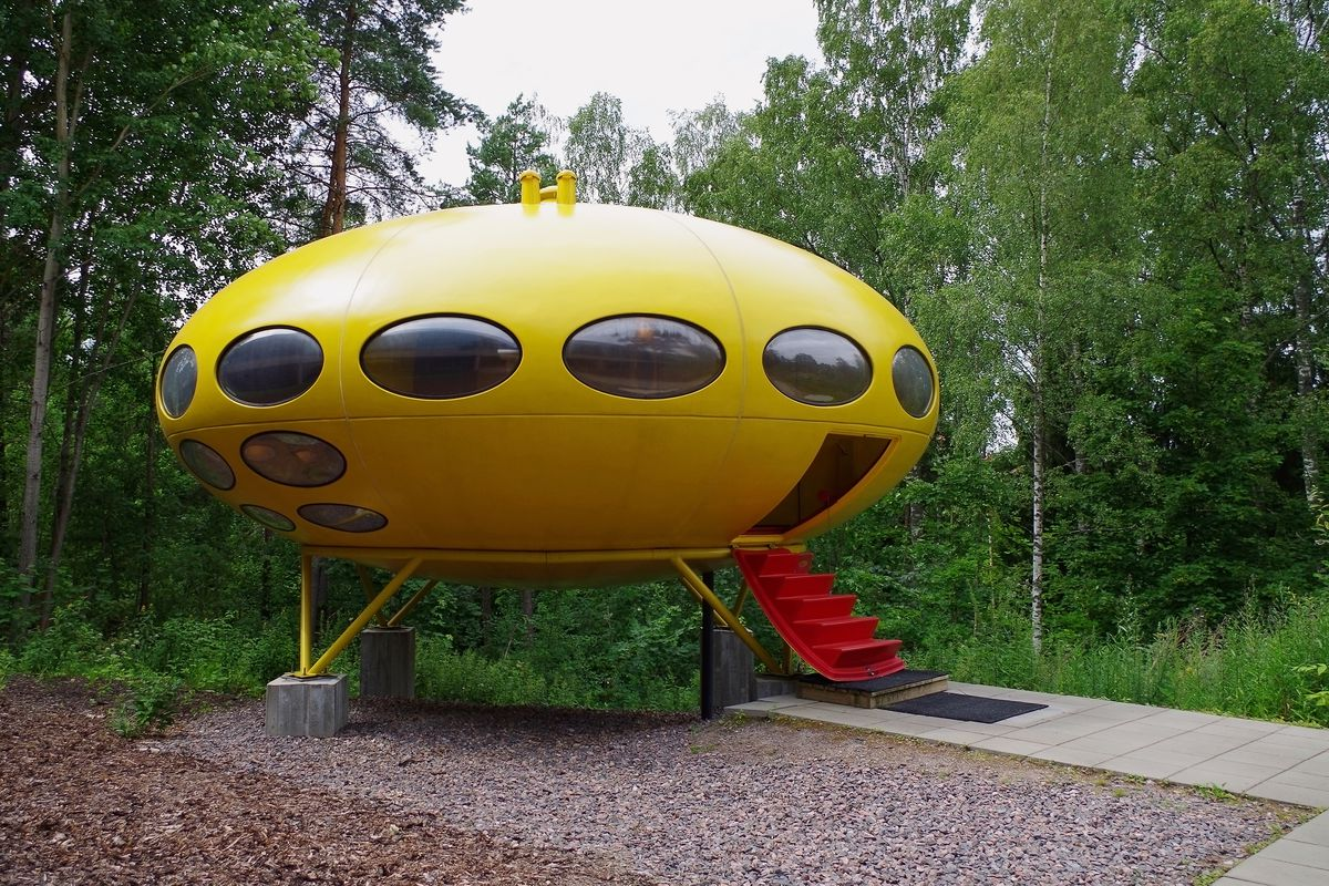 The exterior of a yellow Futuro House in Finland. The house is shaped like a spaceship with oval windows and a red stair case.