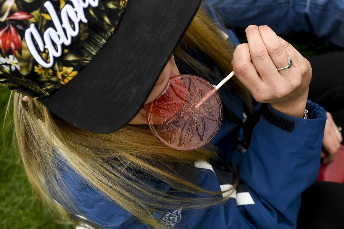 An overhead photo of a woman with dark blond hair and a baseball cap, her face obscured by the brim, eating a large lollipop with a marijuana leaf imprinted on it.
