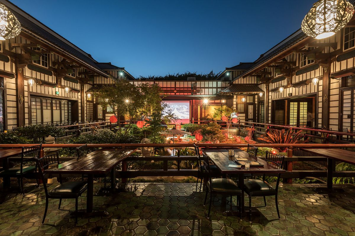 Yamashiro Hollywood's inner courtyard with lots of wood and carvings and Asian art, shown at dusk.