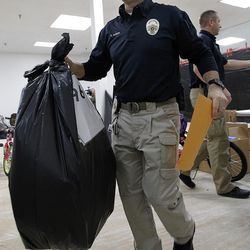 West Valley City Police Officer Devin Novara carries a bag full of presents at the 13th annual Giving Tree program at Valley Fair Mall in West Valley City on Tuesday, Dec. 15, 2015. Novara started the charity, which collects $50,000 to $60,000 in donations annually. The program provides Christmas presents to 170 children from 61 low-income families in the city.