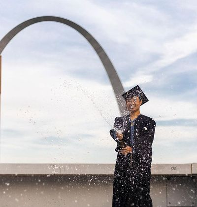 Anh Nguyen celebrates his college graduation with St. Louis' iconic Gateway Arch in the background.