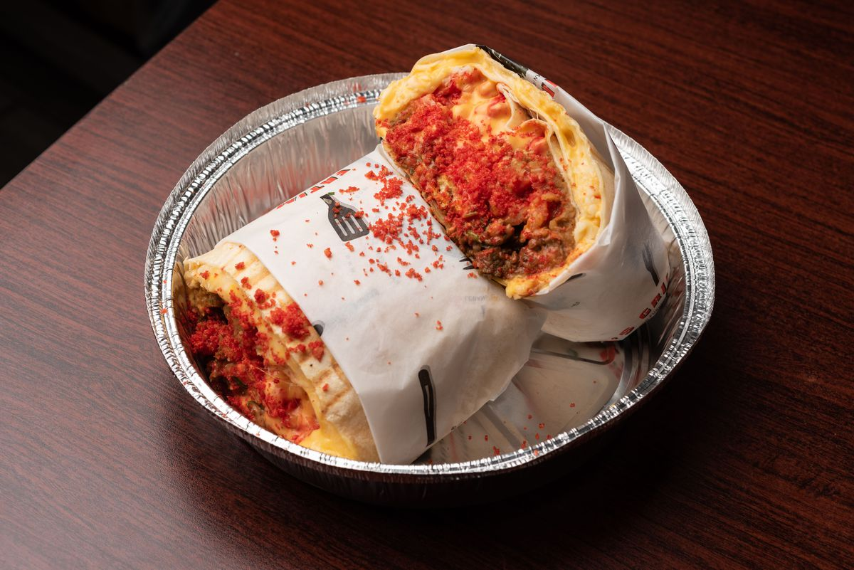 A tin container shows a Hot Cheetos crusted quesadilla brimmimg with cheese.