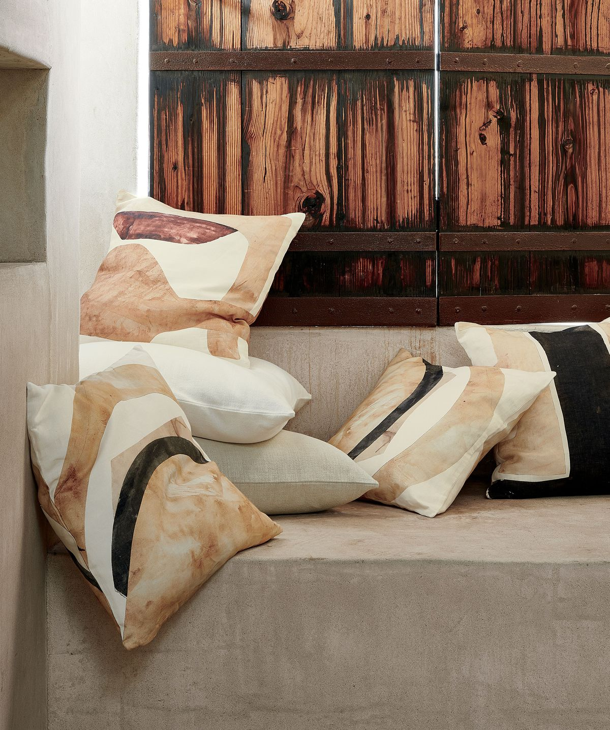 Pile of pillows in earth tones.