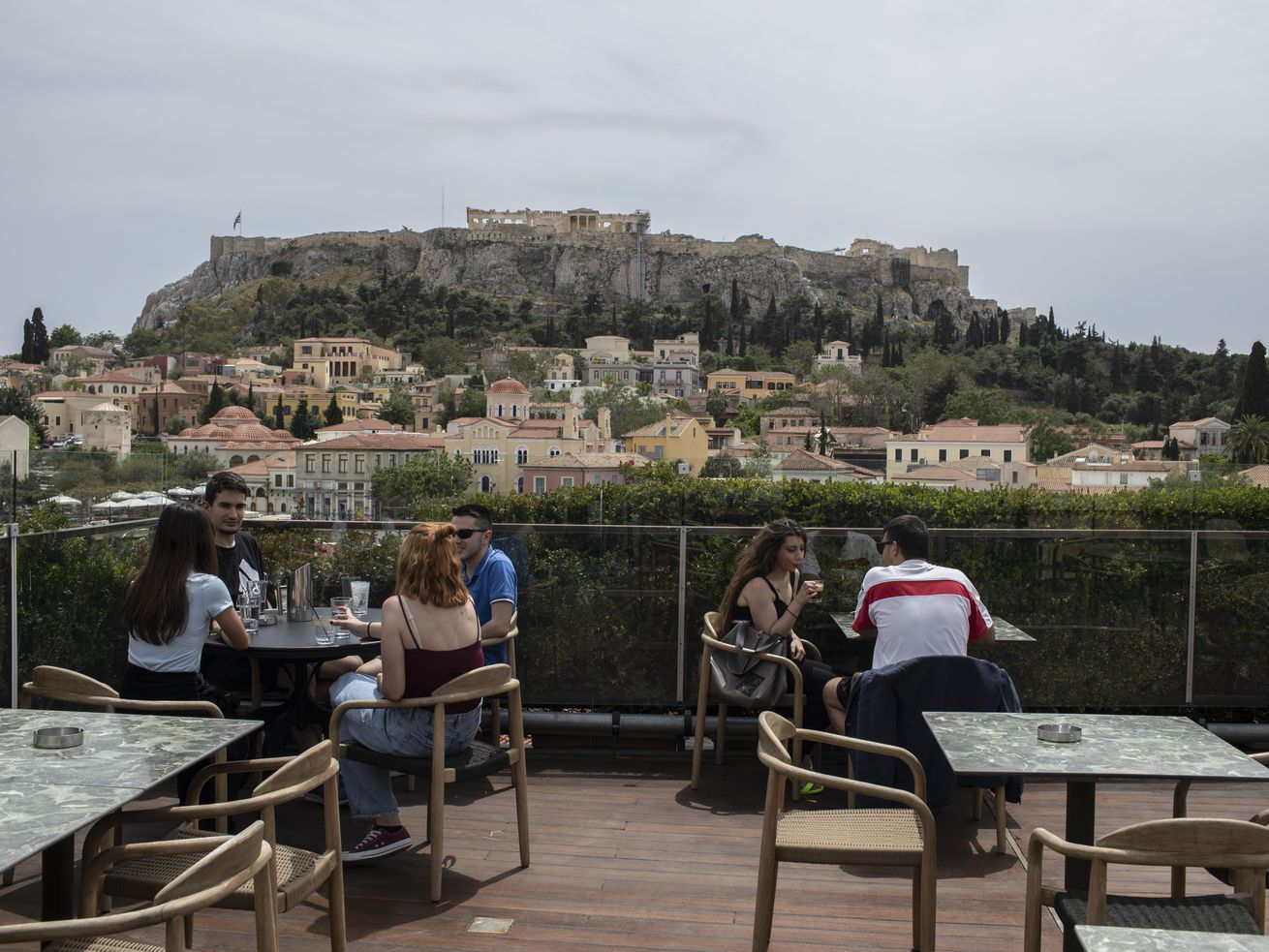 People sit in on a cafe terrace, in the Monastiraki district of Athens, with the ancient Acropolis hill in the background, Monday, May 3, 2021.