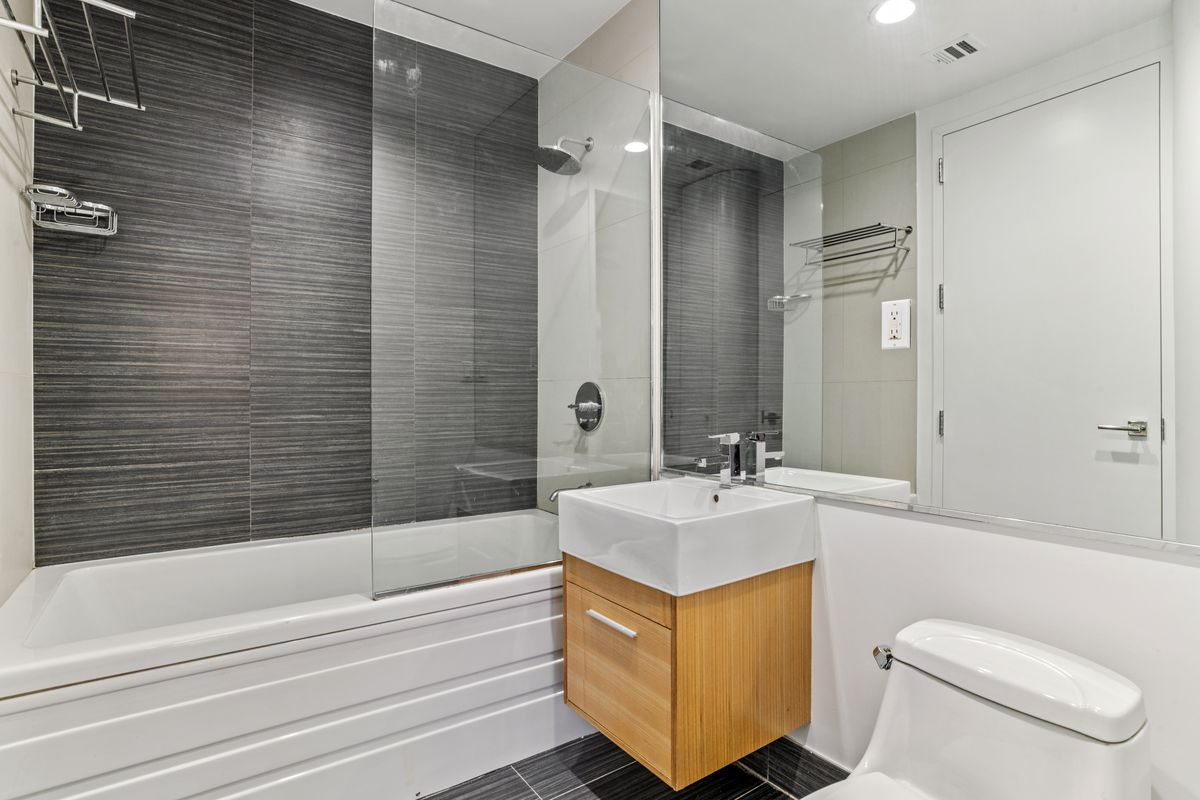A bathroom with dark grey and white walls.