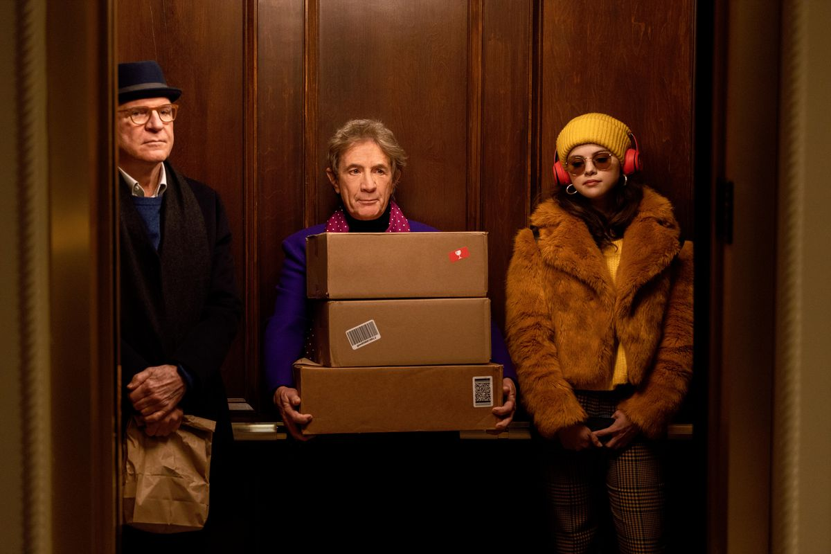 Three people standing in an elevator, with the person in the middle carrying a stack of shipping boxes.