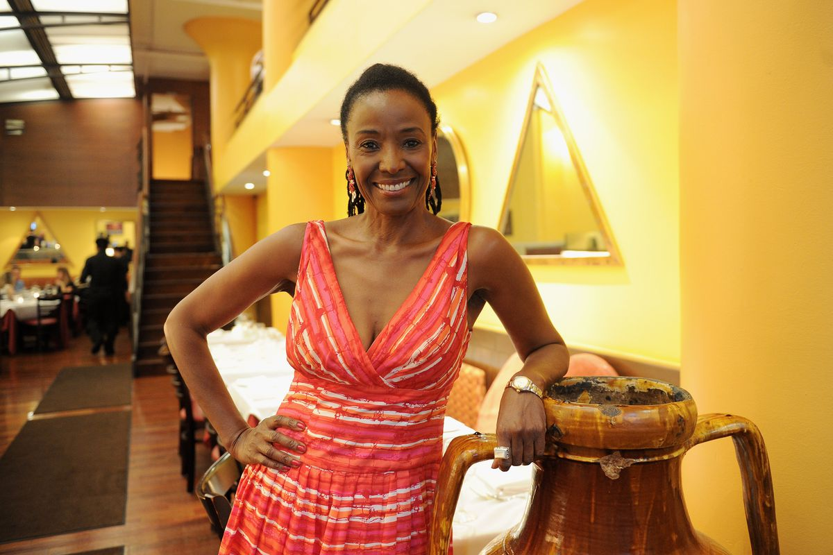 B. Smith wears a red dress and smiles for the camera while at her restaurant in New York City, B. Smith