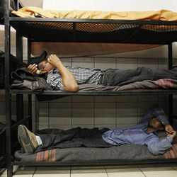 Antonio Perez, bottom, joins dozens of immigrants, many of them Mexican citizens, as they relax in sleeping quarters at a well known immigrant shelter, as many are making tough decisions on whether to try their luck at trying to make it to the United States, by illegally crossing the border, Thursday, Aug. 9, 2012, in Nogales, Mexico.  The U.S. government has halted flights home for Mexicans caught entering the country illegally in the deadly summer heat of Arizona's deserts, a money-saving move that ends a seven-year experiment that cost taxpayers nearly $100 million.(AP Photo/Ross D. Franklin)