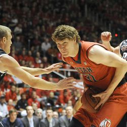 Utah Utes center Dallin Bachynski (31) works his way to the basket between Brigham Young Cougars guard Tyler Haws (3) and Brigham Young Cougars forward Eric Mika (00) during a game at the Jon M. Huntsman Center on Saturday, December 14, 2013.