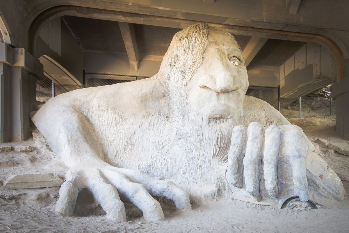 A large public art sculpture of a troll under a bridge made out of cement in Fremont, Seattle