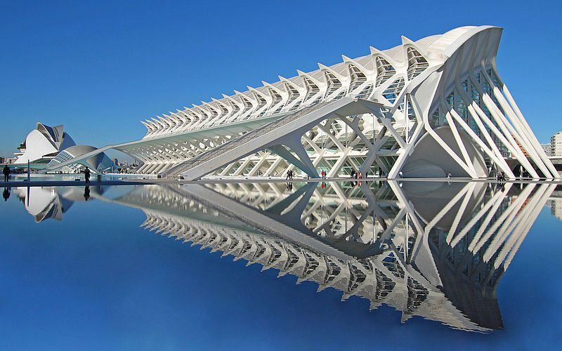 The exterior of the City of Arts and Sciences in Spain. The facade is white and geometric. There is a shallow pool in the foreground that surrounds the structure. There is a person next to the building in the distance.