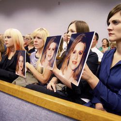 Family members of Martin Joseph MacNeill display photos of Michele MacNeill facing him during a court appearance on Aug. 27, 2012. On Monday, a judge declined to disqualify the Utah County Attorney's Office from prosecuting him.