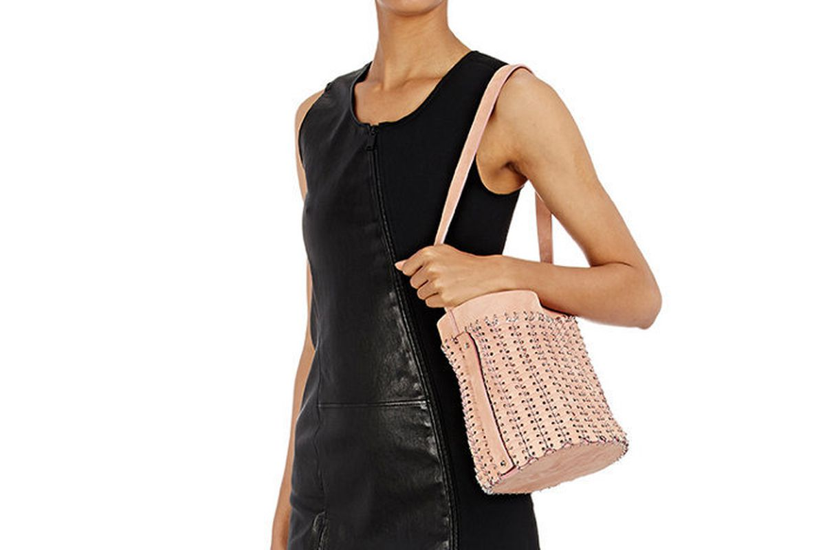 A model in a black leather dress holding a pink bucket bag