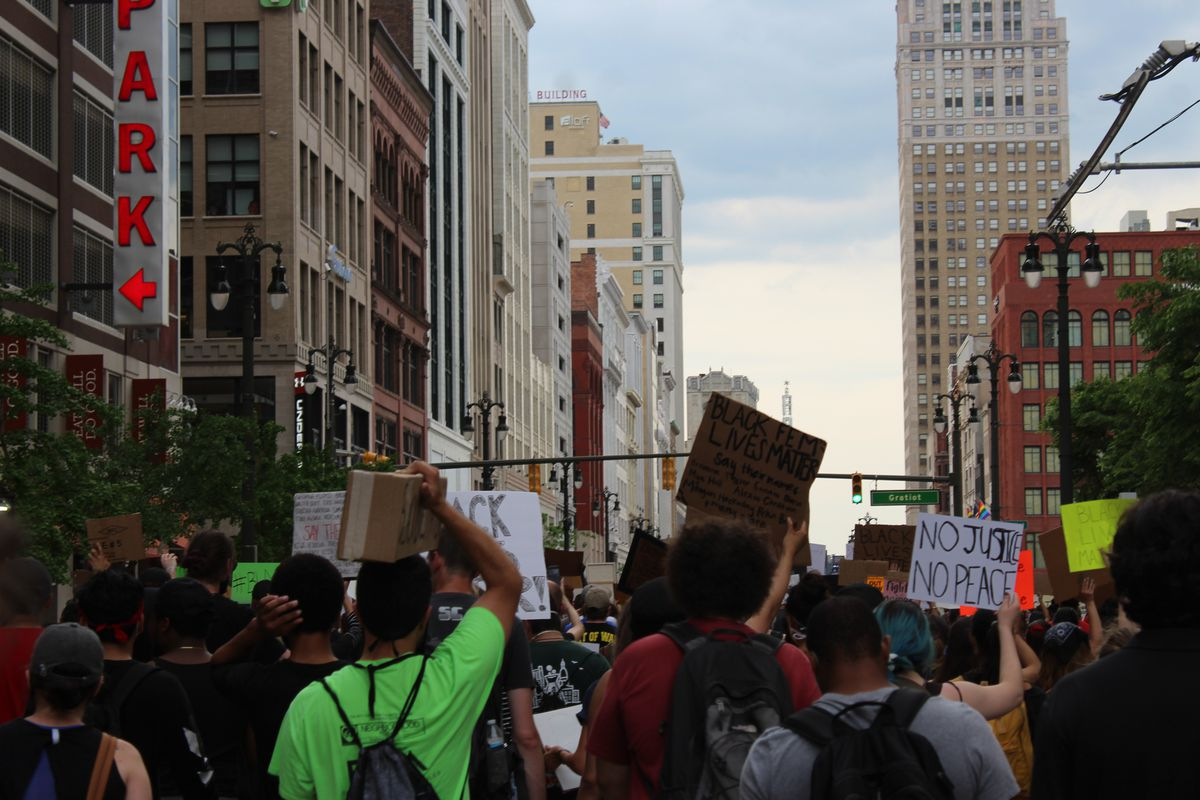 Protesters march in downtown Detroit holding signs in response to the killing of George Floyd in Minneapolis.