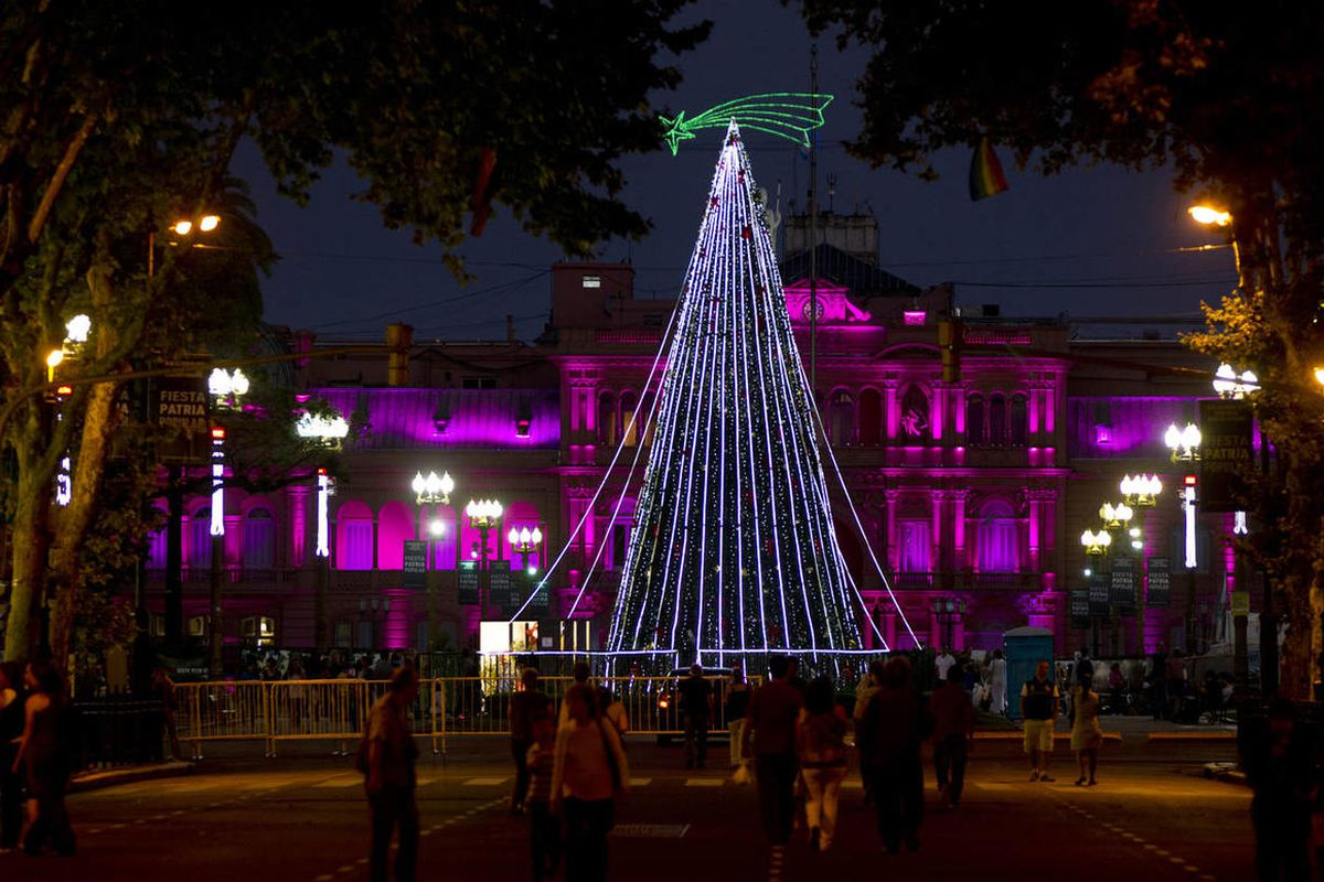 People walk towards a Christmas tree at Plaza de Mayo, back dropped by the government house, in Buenos Aires, Argentina.