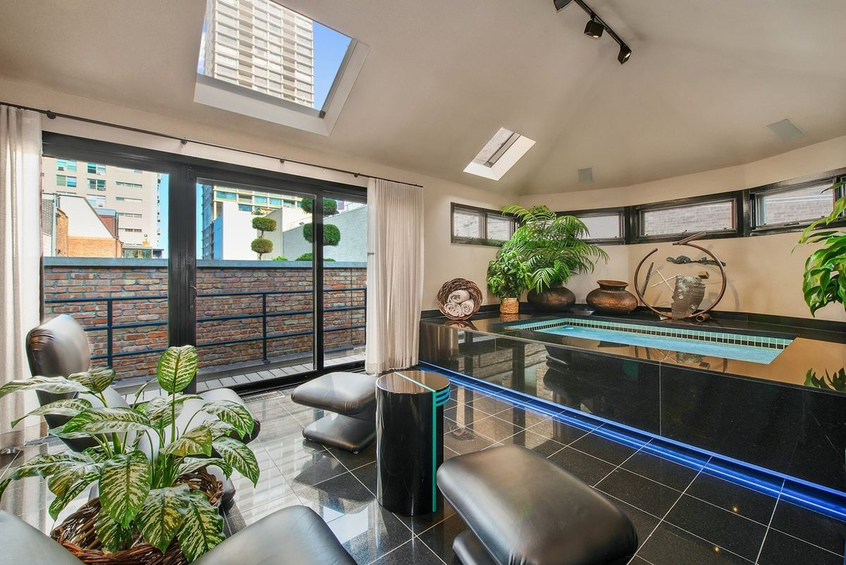 A top floor space with a skylight and balcony. There is an indoor hot tub with black tile and a blue accent light. There are leather chairs and potted plants.