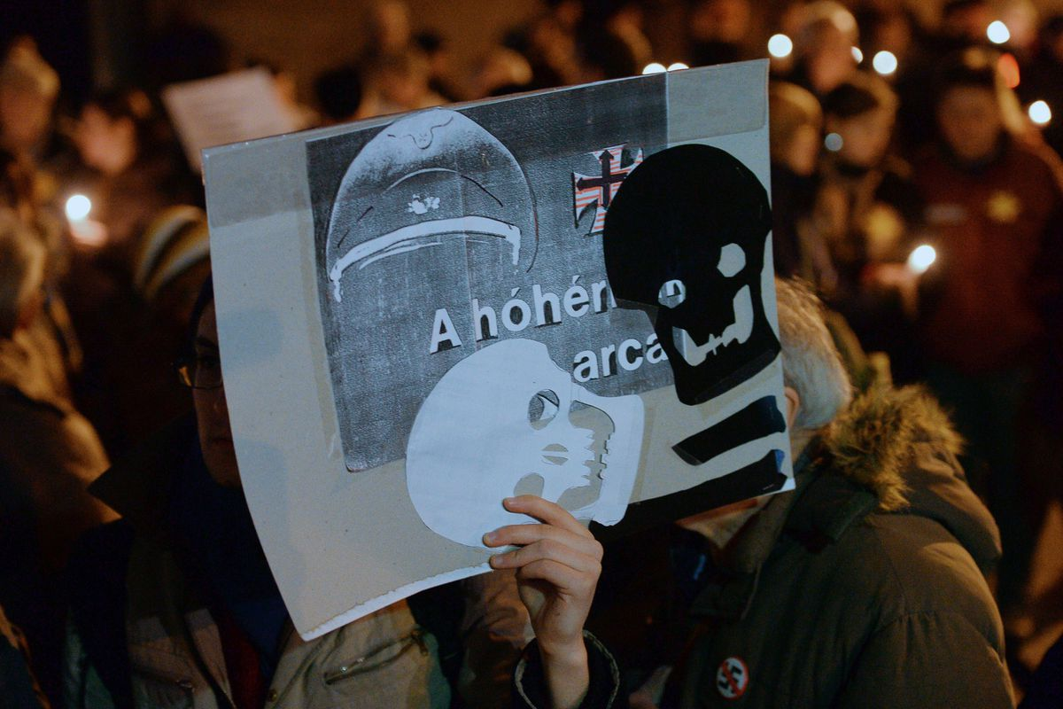 """Members of the Hungarian Jewish community protest Jobbik, a far-right anti-Semitic party. The sign reads """"the face of the executioner."""""""