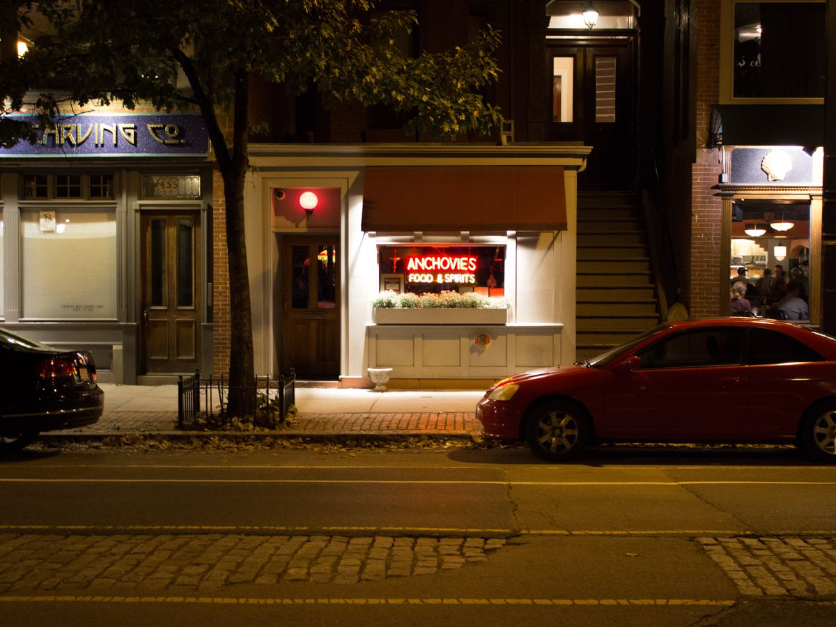 A restaurant exterior by night. Neon signage in its window reads Anchovies Food & Spirits.