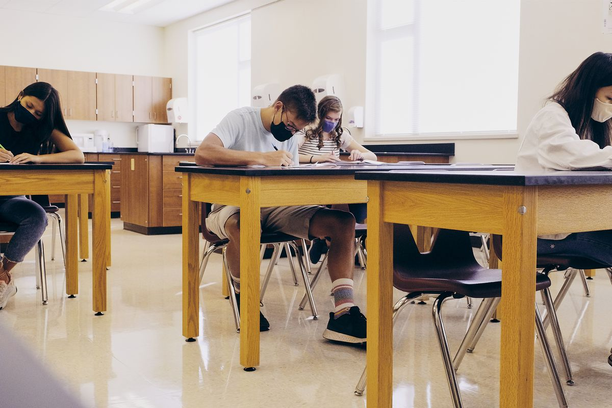 High school students wearing masks sit several feet apart at desks in a classroom,