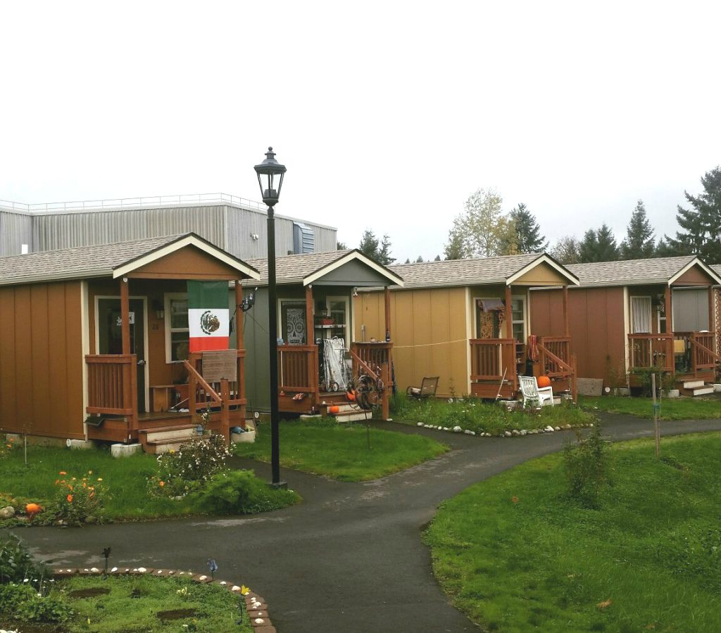 A row of tiny houses. The houses are brown and tan and each house has a sloped roof.