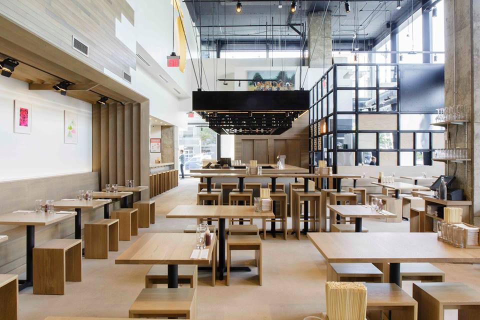 A sea of wooden tables and wooden flooring in a brightly-lit space