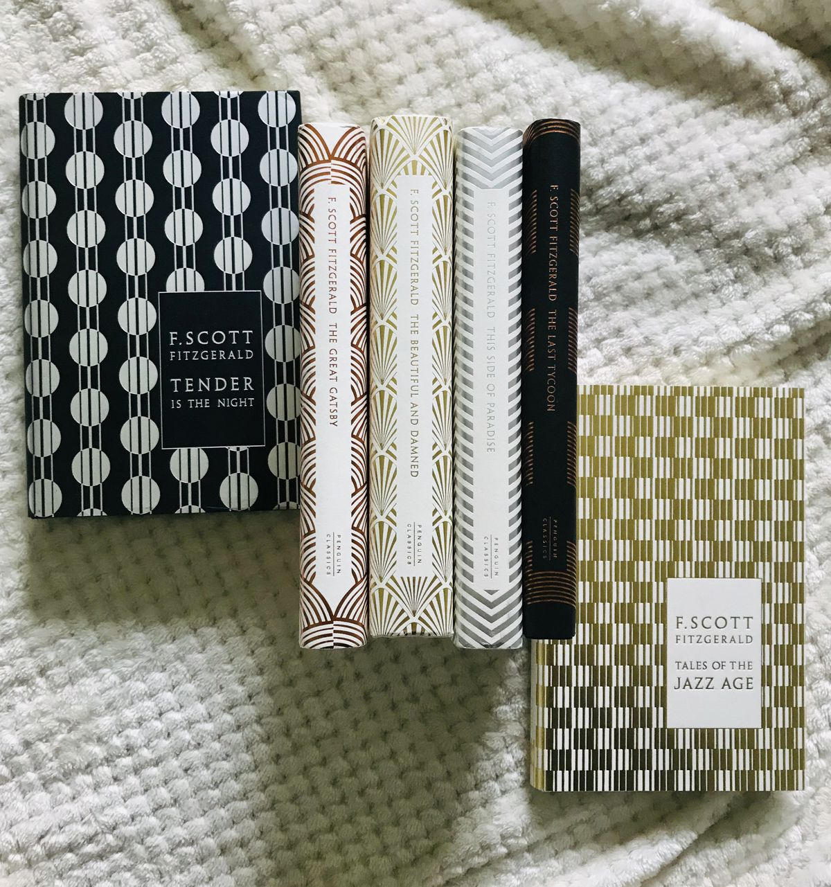 Books with metallic patterned covers sit on a bed.