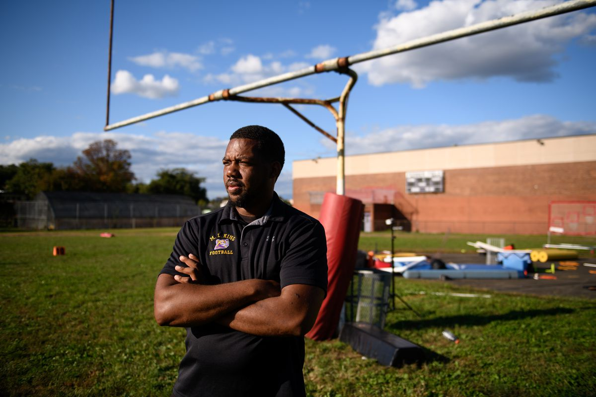 A football coach stands near a goal post on a practice field.