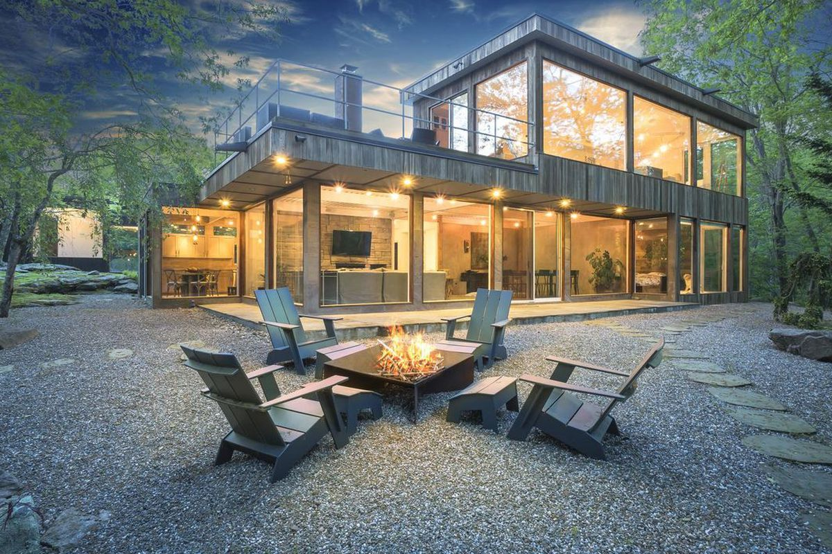 Photo of block glass-walled home on rocky, foresty site with firepit in foreground.
