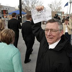 Jim Reynolds holds up a sign asking for tickets to the Saturday morning conference session.