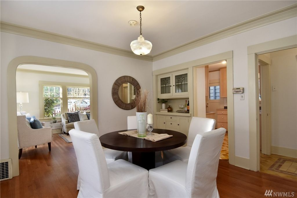 A dining room with a built-in hutch and an arched doorway leading back to the living room