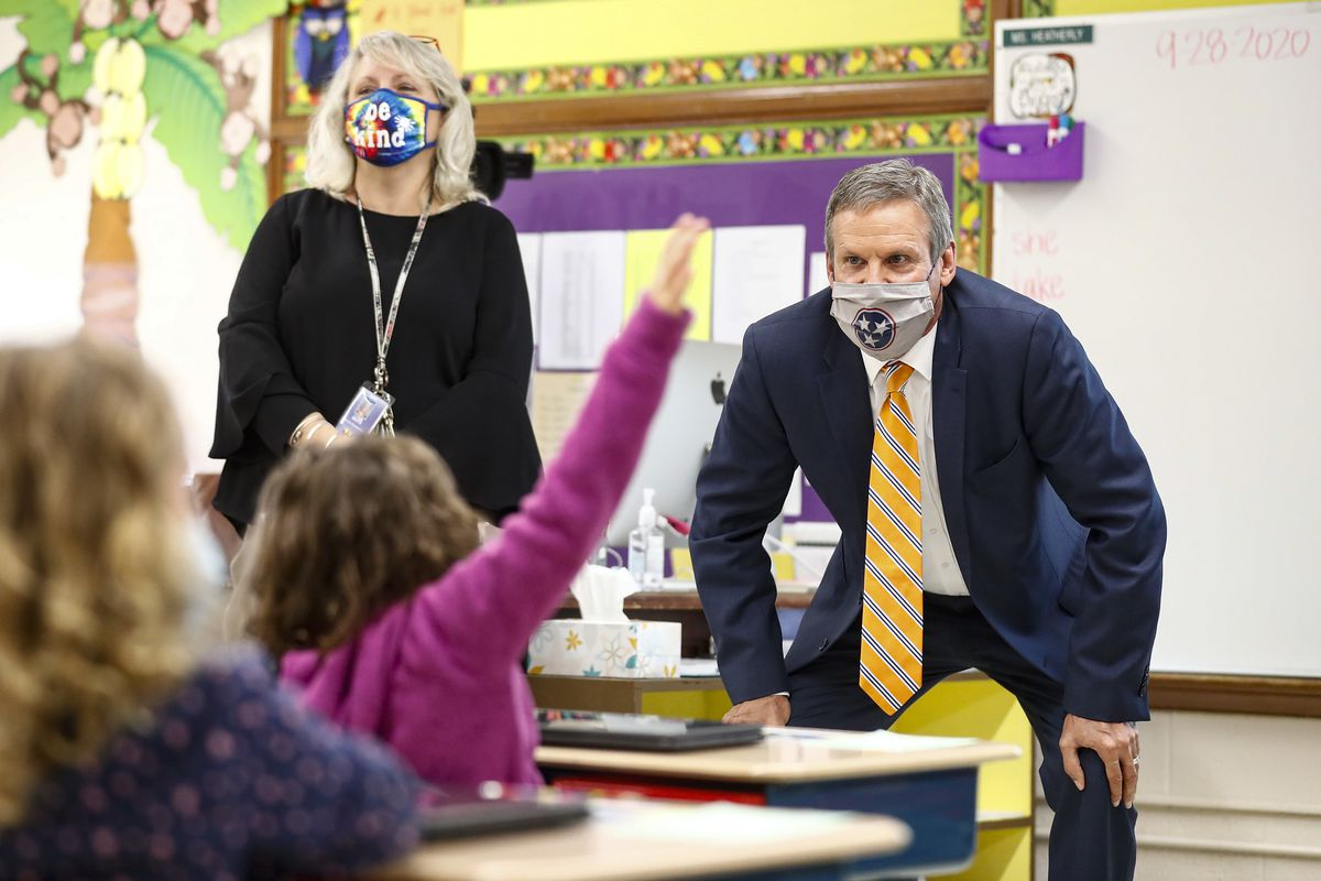 Gov. Bill Lee squats to talk to elementary students at the front of the classroom while students raise their hands.