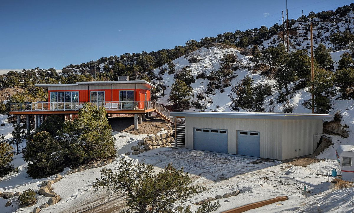 A bright orange shipping container house sits next to a three-car garage in a gray and blue color.