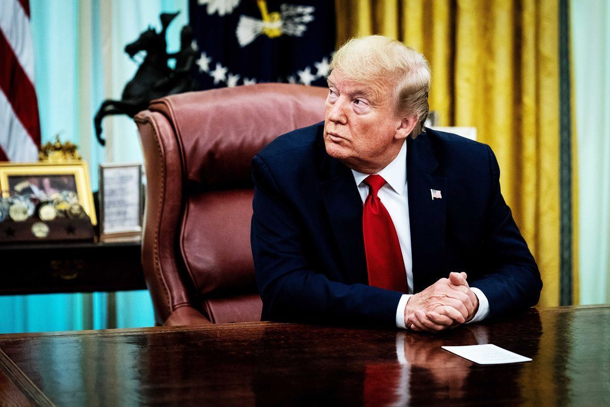 In a dark suit and red tie, Trump frowns seated at his desk in the Oval Office. He looks to his right with his hands clasped.
