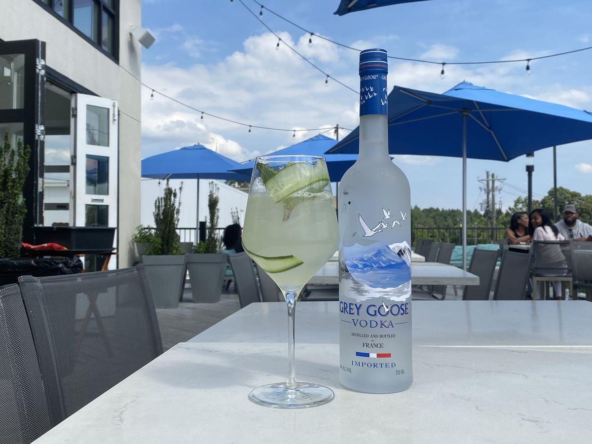 A cocktail in a large wine glass, filled with cucumber slices sits next to a Grey Goose bottle