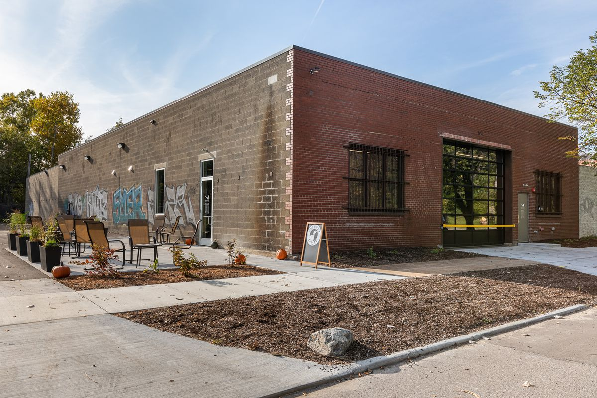 The red brick and concrete block exterior of Brewery Faisan, including a small patio area, is shown on a sunny fall afternoon. The front of the building features a garage door-style window and there are pumpkins on the patio.